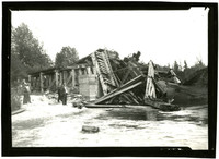 A Bloedel-Donovan train engine and railroad bridge have collapsed into small river, with several people looking on from shore