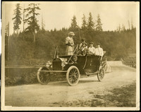 Five people in an early convertible automobile  stopped on a dirt lane by a small lake and forested hills