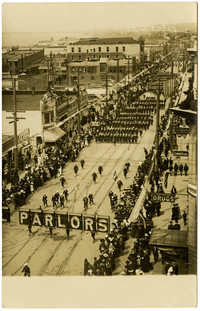 View from above of parade marching down Holly street, with spectators lining the street, Bellingham, Washington