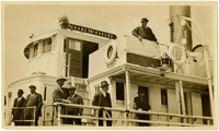 Several men stand on deck and bridge deck of steamship