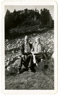 Older man and woman seated on a scree slope
