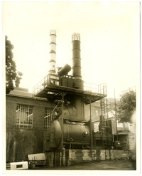 Exterior of brick building with incinerator or boiler equipment and exhaust stacks adjacent