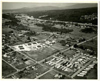 Aerial view of a trailer (or similar looking houses) park and a development of several low buildings set amidst rural farmland with I-5 in the middle ground and mountains in the background