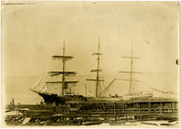 Three-masted lumber ship at Sehome dock with lumber stacked on dock and floating in water