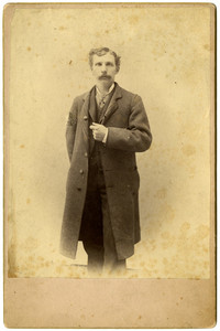 Portrait of man standing in suit and long coat