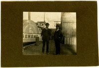 """Two men in suits stand on dock with sidewheeler boat """"Sehome I"""" in background"""