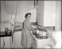Unidentified woman wearing a striped dress and checkered apron standing at a sink washing dishes.