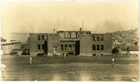 Students play baseball in field adjacent to burned structure of Fairhaven High School, Bellingham, WA