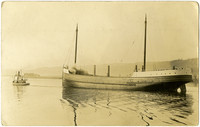 A large sail/steam ship is towed by tugboat
