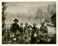 A man, a woman, and six children sit for pose in clearing near cabin