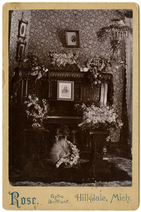 An ornately carved upright piano is arrayed with flower arrangements surrounding a framed photograph of a man, in memoriam