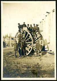 Eleven men stand in front of and sit atop a large wooden wheel used with oxen to haul logs to lumber mill