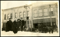 Four people bundled in coats on snowy city streets with a horse-drawn sled in background