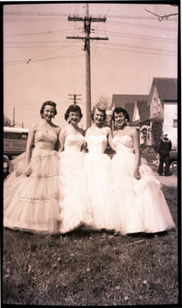 Four women in formal dresses, possibly as part of beauty pageant, stand in row