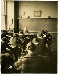 Classroom with students at desks, woman teacher sits at front of room