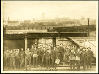 Great Northern railroad cars travel along elevated tracks on Bellingham Bay, with piers, warehouses, piles of lumber in background, and separate photograph attached below