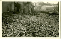 Postcard of five workers waist-deep in huge bin of empty metal food cans and paper, next to several workers standing in front of warehouse or factory