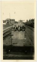 Three men sit atop wooden crates on railroad flatcar