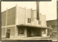 Two women walk towards front exterior of Paramount Theater, Mount Vernon, WA