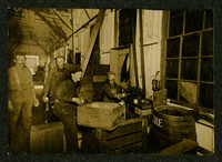 Mr. Jensen, Roy Weaver, Hardy Getty, and one unidetified mand stand among boxes and equipment of canning warehouse at the American Can Company