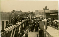 Large crowd gathered on dock with warehouses and city of Bellingham, WA, in background