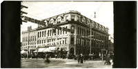 """View from across intersection of three-story stone building called """"The Sunset Block"""" with groundfloor storefronts, and """"New York Dental Parlors"""" banner hanging over street between buildings"""
