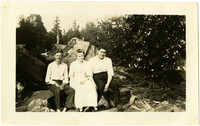 A woman and two men sitting on large stump with forest in background