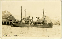 "Two fishing vessels, ""S.S. Canada"" and ""S.S. Imbricaria"" are moored at docks of King, Cove, AK"