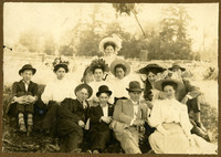 Group of young men and women pose seated in a field, wearing Sunday finery