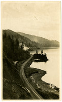 Mountainside track of Great Northern railroad along lake shore, steam engine in distance