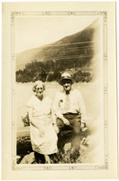 Older man and woman sit on log next to lake or bay, with forested hills in distance