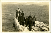 Several men stand on bow of commercial fishing boat at sea, boat rails and equipment covered in ice
