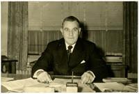 Unidentified man in pinstripe suit sits behind desk in office