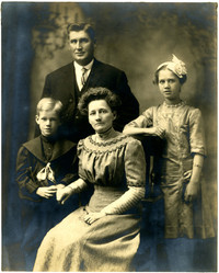 Studio portrait of family of four with mother seated in center