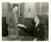 A man in a suit seated behind a desk hands a check to a man standing beside him