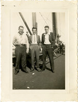 Three men stand for photograph on deck of the M.S. Clevedon