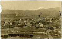View from above of early Sumas, Washington with railroad tracks in foreground and Mt. Baker on the horizon