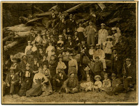 Large group of people pose on gravelly beach with large pile of logs