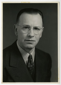 Studio portrait of Axel Olson in spectacles and suit and tie