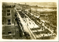 Long procession of marching sailors seen from upper story of building, looking south along State street, with ships anchored in Bellingham Bay in distance