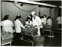 Man in labcoat and cap stands next to women packing crab legs into boxes at work station