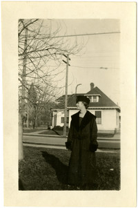 Woman in fur-trimmed hat and coat stands in front yard, looking to her right