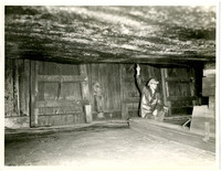 unidentified man sitting below what is probably the hull of a ship, pointing to a spot on the hull