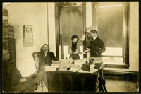 Two men sit, and a woman and man stand, in office with desk coverd in books and papers