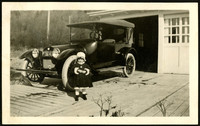 A little girl in a fancy coat poses in front of a fine early model car parked outside a garage