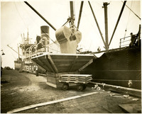 Wheat being unloaded dockside from large Luchenbach freight vessel into hopper