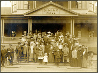 Group of over fifty men, women and children standing on the porch steps of a unidentified Queen Anne house