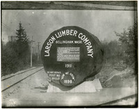 Sign for entrance to Larson Lumber Company next to railway, made from large log round