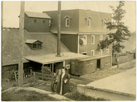 Woman stands on grassy landing above railroad tracks with depot and attached warehouse on opposite side