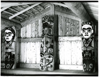 Totem poles with realistic and abstract figures of humans, fish, animals, on façade of longhouse at Kasaan, Alaska